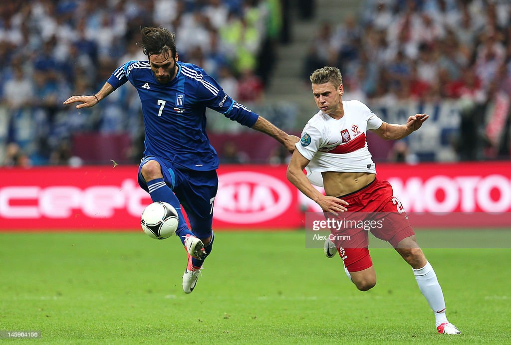 Giorgos Samaras of Greece controls the ball ahead of Lukasz Piszczek of Poland during the UEFA EURO 2012 group A match between Poland and Greece at National Stadium on June 8, 2012 in Warsaw, Poland.