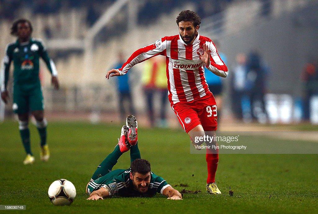 Giorgos Seitaridis of Panathinaikos falls as Djamel Abdoun of Olympiacos attacks during the Superleague match between Panathinaikos FC and Olympiacos Piraeus at OAKA Stadium on December 9, 2012 in Athens, Greece.