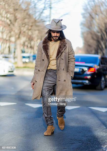 Giotto Calendoli is wearing a coat hat grey pants boots is seen at Armani during Milan Men's Fashion Week Fall/Winter 2017/18 on January 14 2017 in...