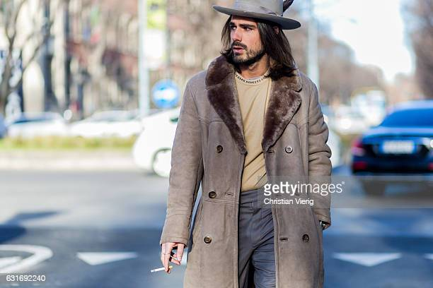 Giotto Calendoli is wearing a coat hat grey pants is seen at Armani during Milan Men's Fashion Week Fall/Winter 2017/18 on January 14 2017 in Milan...