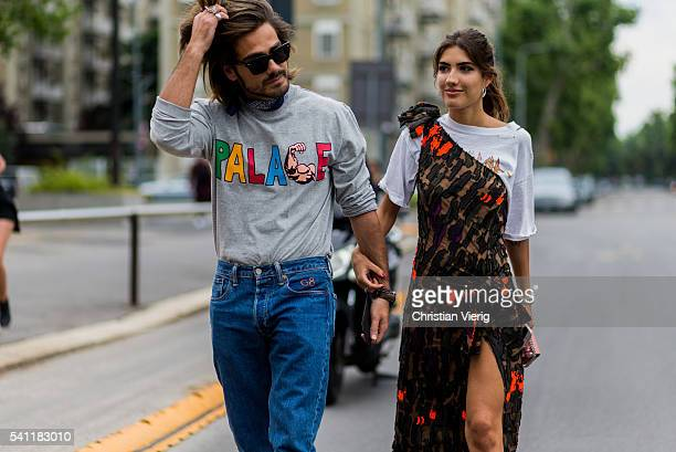 Giotto Calendoli wearing a grey Palace sweater and denim jeans and bandana and Patricia Manfield outside Versace during the Milan Men's Fashion Week...