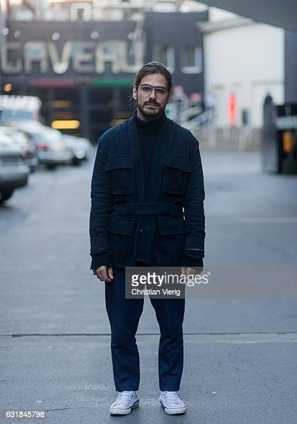 Giotto Calendoli wearing wearing a navy jacket navy pants Converse sneakers glasses at Etro during Milan Men's Fashion Week Fall/Winter 2017/18 on...