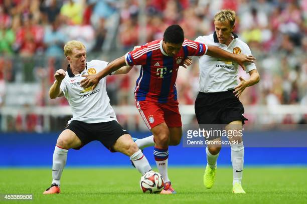 Giovane Elber of FCB AllStars is challenged by Paul Scholes and Phil Neville of ManUtd Legends during the friendly match between FC Bayern Muenchen...