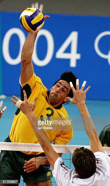 Giovane Gavio of Brazil spikes the ball past Thomas Hoff of the USA at the men's indoor Volleyball preliminary match on August 23 2004 during the...