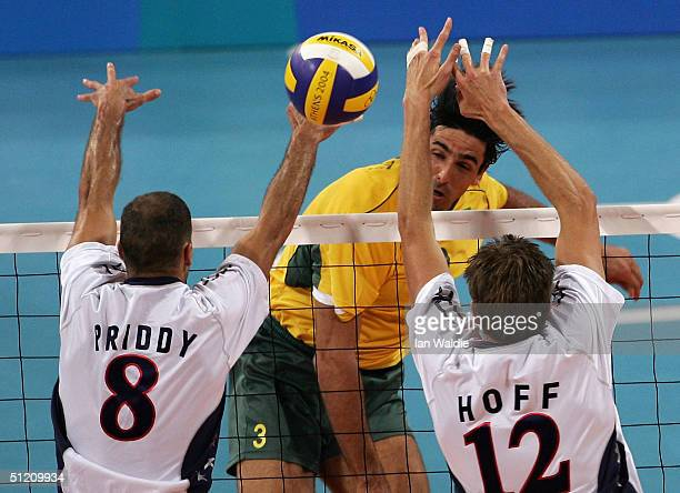 Giovane Gavio of Brazil spikes the ball past William Priddy and Thomas Hoff of the USA at the men's indoor Volleyball preliminary match on August 23...