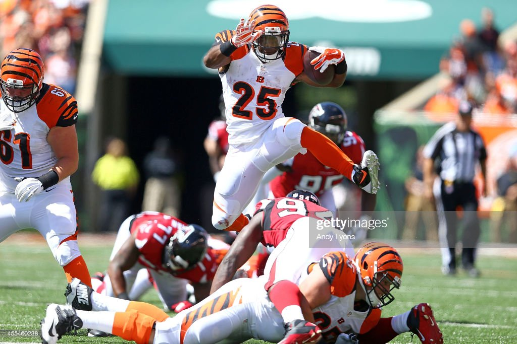 Giovani Bernard of the Cincinnati Bengals jumps over Jonathan Massaquoi of the Atlanta Falcons during the second quarter at Paul Brown Stadium on...