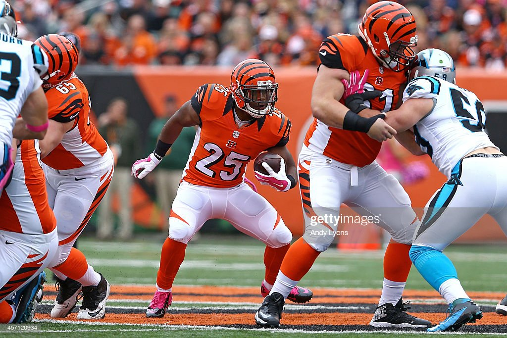 Giovani Bernard of the Cincinnati Bengals looks for an open lane as Russell Bodine of the Cincinnati Bengals blocks Luke Kuechly of the Carolina...