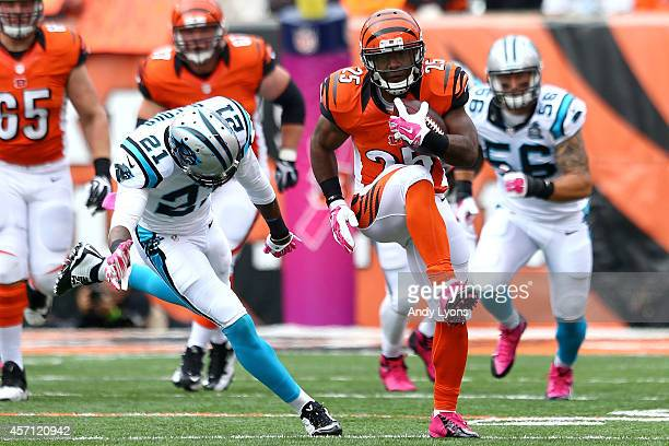 Giovani Bernard of the Cincinnati Bengals slips past Thomas DeCoud of the Carolina Panthers to score on an 89 yard touchdown run during the second...