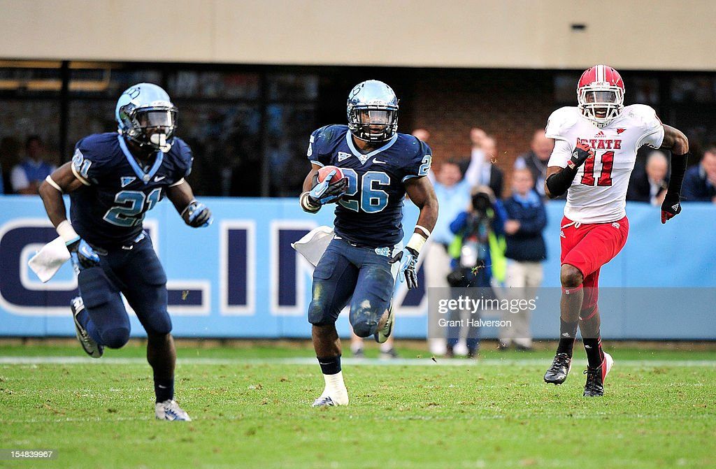 Giovani Bernard #26 of the North Carolina Tar Heels breaks away from Juston Burris #11 of the North Carolina State Wolfpack to score a game-winning touchdown against the North Carolina State Wolfpack at Kenan Stadium on October 27, 2012 in Chapel Hill, North Carolina. North Carolina won 43-35.