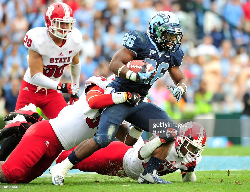 Giovani Bernard #26 of the North Carolina Tar Heels drags Ricky Dowdy #34 and Dontae Johnson #25 of the North Carolina State Wolfpack for extra yardage during play at Kenan Stadium on October 27, 2012 in Chapel Hill, North Carolina. North Carolina won 43-35.