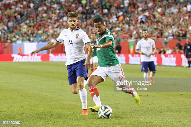 Giovani Dos Santos Mexico gets past Miguel Veloso Portugal during the Portugal V Mexico International Friendly match in preparation for the 2014 FIFA...