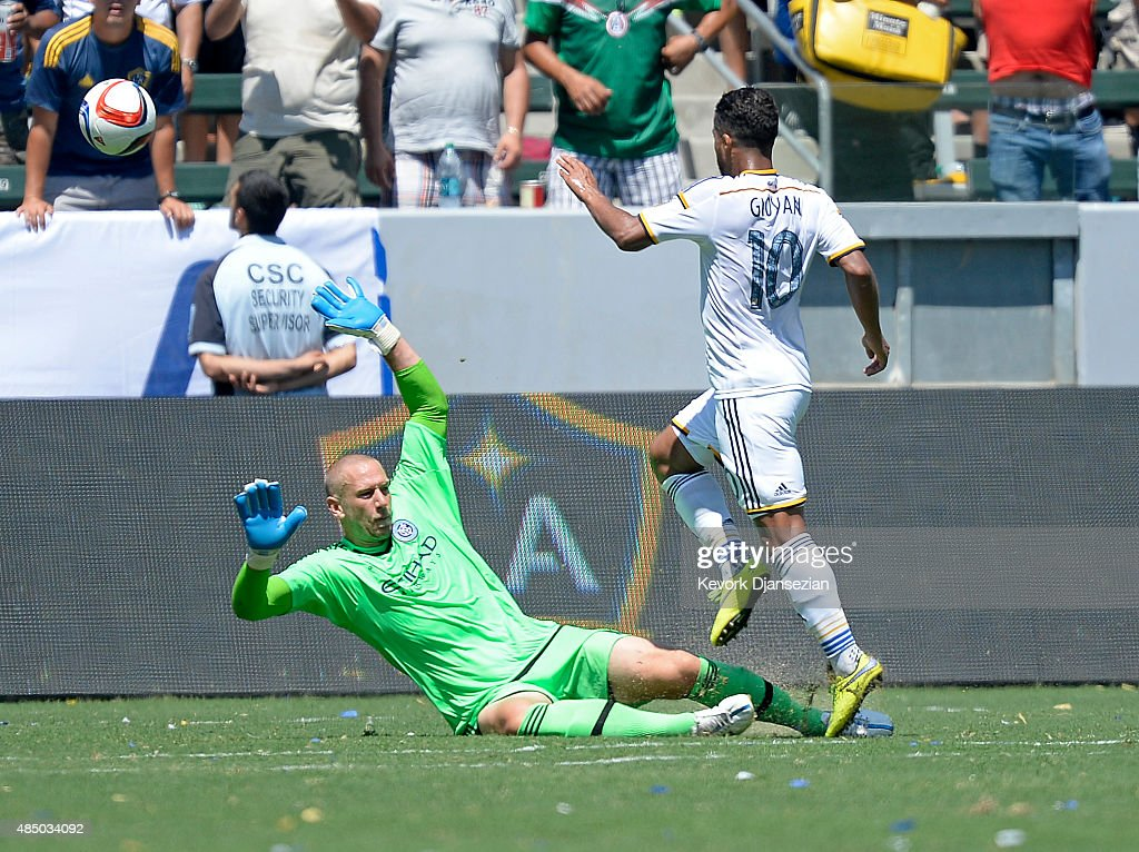 Giovani Dos Santos #10 of Los Angeles Galaxy kicks the ball over goalkeeper Josh Saunders #12 of New York City FC to score a goal during the second half at StubHub Center August 23, 2015, in Carson, California.
