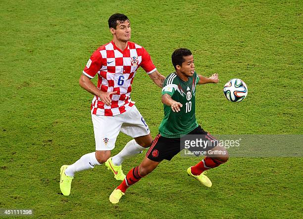 Giovani dos Santos of Mexico controls the ball as Dejan Lovren of Croatia gives chase during the 2014 FIFA World Cup Brazil Group A match between...