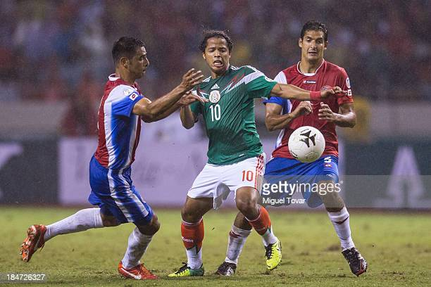 Giovani Dos Santos of Mexico fights for the ball with Michael Umaña Corrales of Costa Rica during a match between Costa Rica and Mexico as part of...