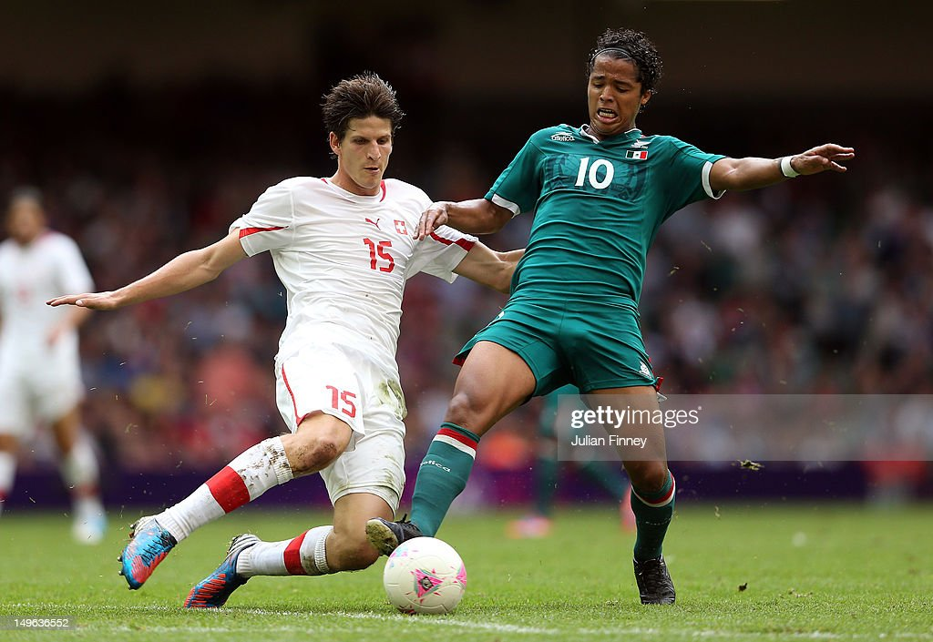 <a gi-track='captionPersonalityLinkClicked' href=/galleries/search?phrase=Giovani+dos+Santos&family=editorial&specificpeople=4435901 ng-click='$event.stopPropagation()'>Giovani dos Santos</a> of Mexico goes for the ball with Timm Klose of Switzerland during the Men's Football first round Group B match between Mexico and Switzerland on Day 5 of the London 2012 Olympic Games at Millennium Stadium on August 1, 2012 in Cardiff, Wales.