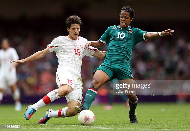 Giovani dos Santos of Mexico goes for the ball with Timm Klose of Switzerland during the Men's Football first round Group B match between Mexico and...