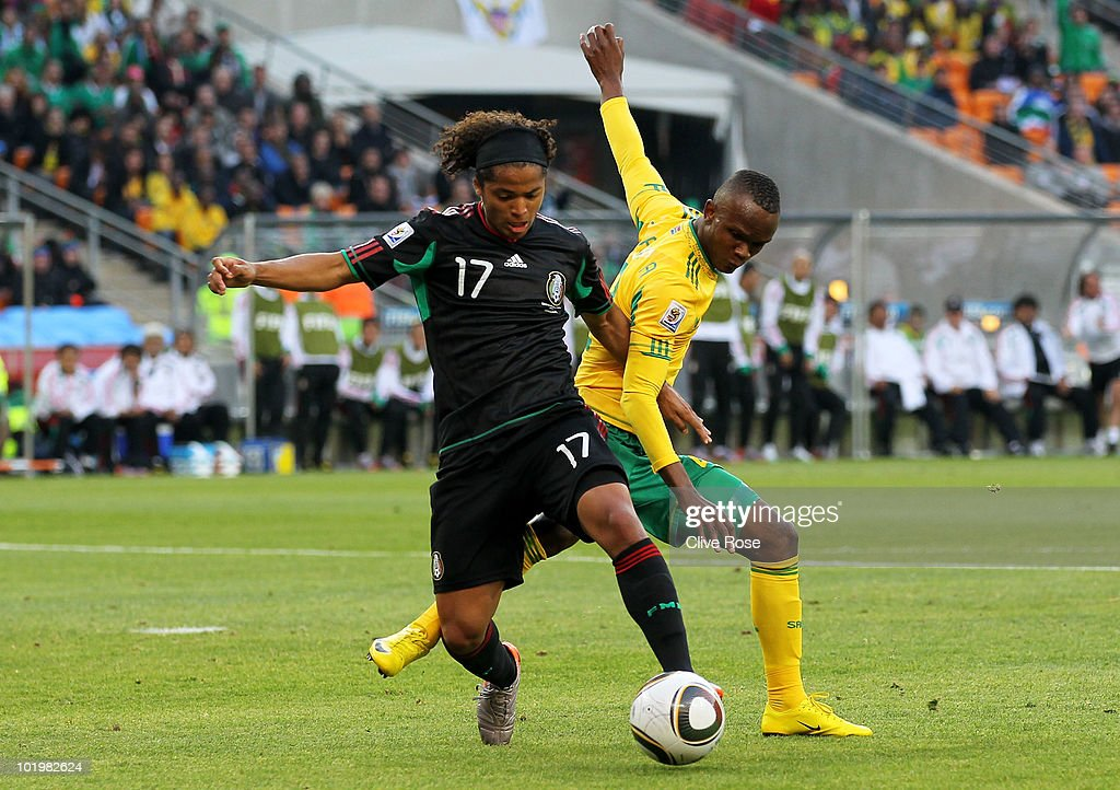 Giovani Dos Santos of Mexico is challenged by Siboniso Gaxa of South Africa during the 2010 FIFA World Cup South Africa Group A match between South...