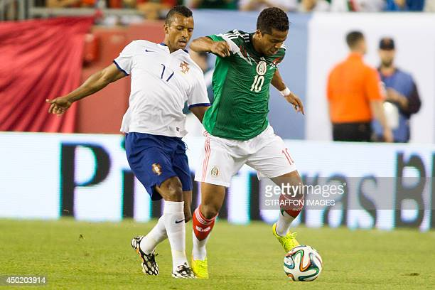 Giovani dos Santos of Mexico runs with the ball as Nani of Portugal tries to chase him during the Internatinal friendly match between Mexico and...