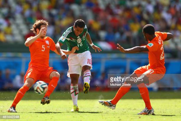 Giovani dos Santos of Mexico shoots and scores his team's first goal against Daley Blind and Georginio Wijnaldum of the Netherlands during the 2014...