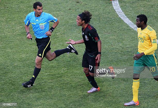 Giovani Dos Santos of Mexico speaks with referee Ravshan Irmatov during the 2010 FIFA World Cup South Africa Group A match between South Africa and...