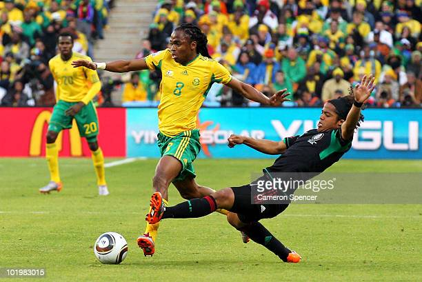 Giovani Dos Santos of Mexico tackles Siphiwe Tshabalala of South Africa during the 2010 FIFA World Cup South Africa Group A match between South...