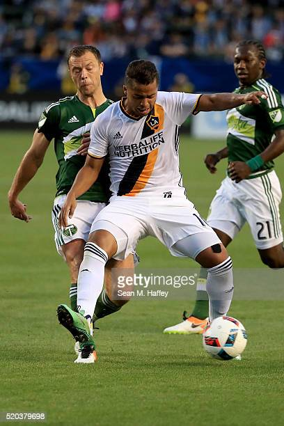 Giovani dos Santos of the Los Angeles Galaxy dribbles past Jack Jewsbury of the Portland Timbers during the first half of their MLS match at StubHub...