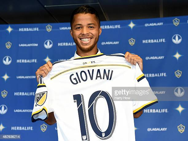 Giovani Dos Santos of the Los Angeles Galaxy holds up his new jersey at a press conference at StubHub Center on August 4 2015 in Carson California