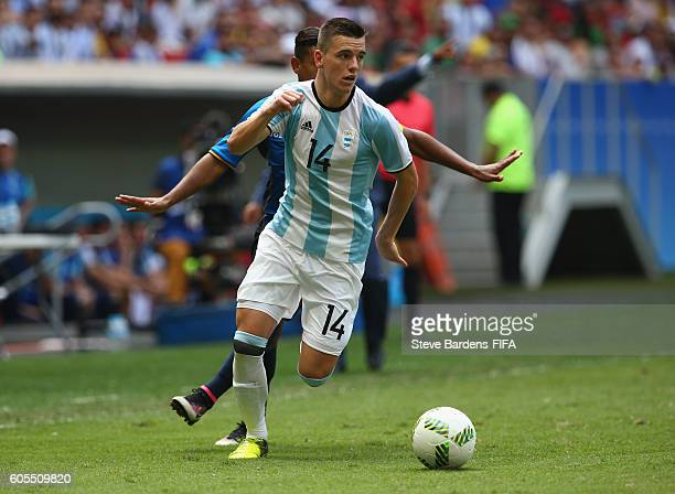 Giovani Lo Celso of Argentina and Bryan Acosta of Honduras challenge for the ball during the Men's First Round Group D match between Argentina and...