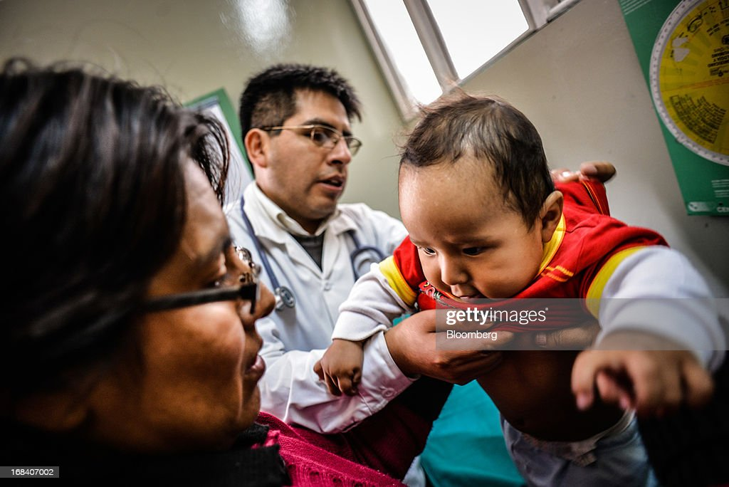 Giovanna Arroya, left, holds her son, Paolo, while he receives an exam from clinic doctor Herbert Damian at the health clinic in the town of La Oroya, Peru, on Thursday, March 21, 2013. Most of La Oroyaís children suffer elevated lead levels, according to the Peruvian government. The question of responsibility for lead pollution in La Oroya is at the center of high-stakes clash between Peru and U.S. billionaire Ira Rennert, who owned Doe Run Peru for more than a decade through Renco Group Inc., a metals, mining and industrial conglomerate based in New York that has said it is not responsible for the childrenís ills. Photographer: Meridith Kohut/Bloomberg via Getty Images