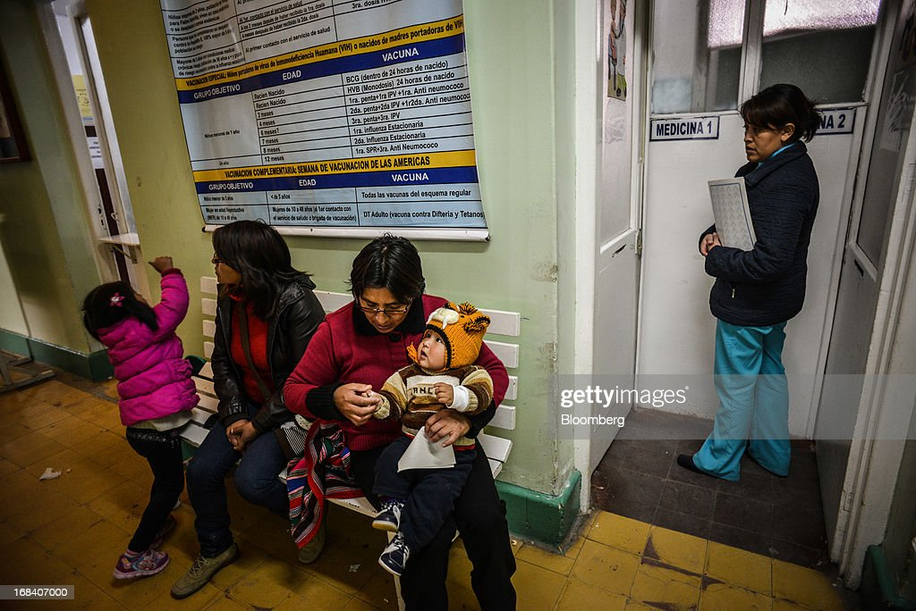 Giovanna Arroya, second right, sits with her son, Paolo, while they await for an exam from a doctor at La Oroya's health clinic, in the town of La Oroya, Peru, on Thursday, March 21, 2013. Most of La Oroyaís children suffer elevated lead levels, according to the Peruvian government. The question of responsibility for lead pollution in La Oroya is at the center of high-stakes clash between Peru and U.S. billionaire Ira Rennert, who owned Doe Run Peru for more than a decade through Renco Group Inc., a metals, mining and industrial conglomerate based in New York that has said it is not responsible for the childrenís ills. Photographer: Meridith Kohut/Bloomberg via Getty Images