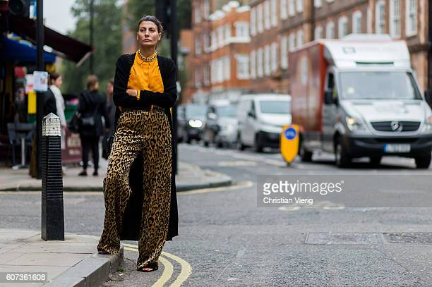 Giovanna Battaglia wearing a yellow button shirt leo print pants and black cardigan outside of JW Anderson during London Fashion Week Spring/Summer...