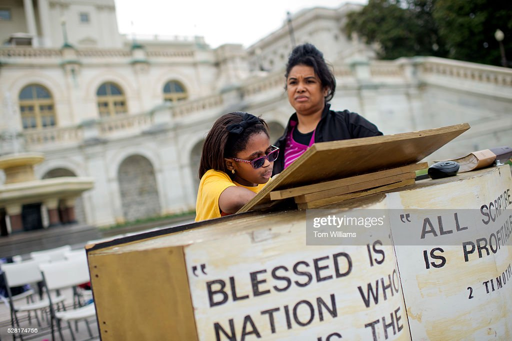 Giovanna Quaynor, 9, and Sandra Nelson, members of Christ Chapel in Woodbridge, Va., participate in the 27th annual U.S. Capitol Bible Reading Marathon on the West Front, May 4, 2016.