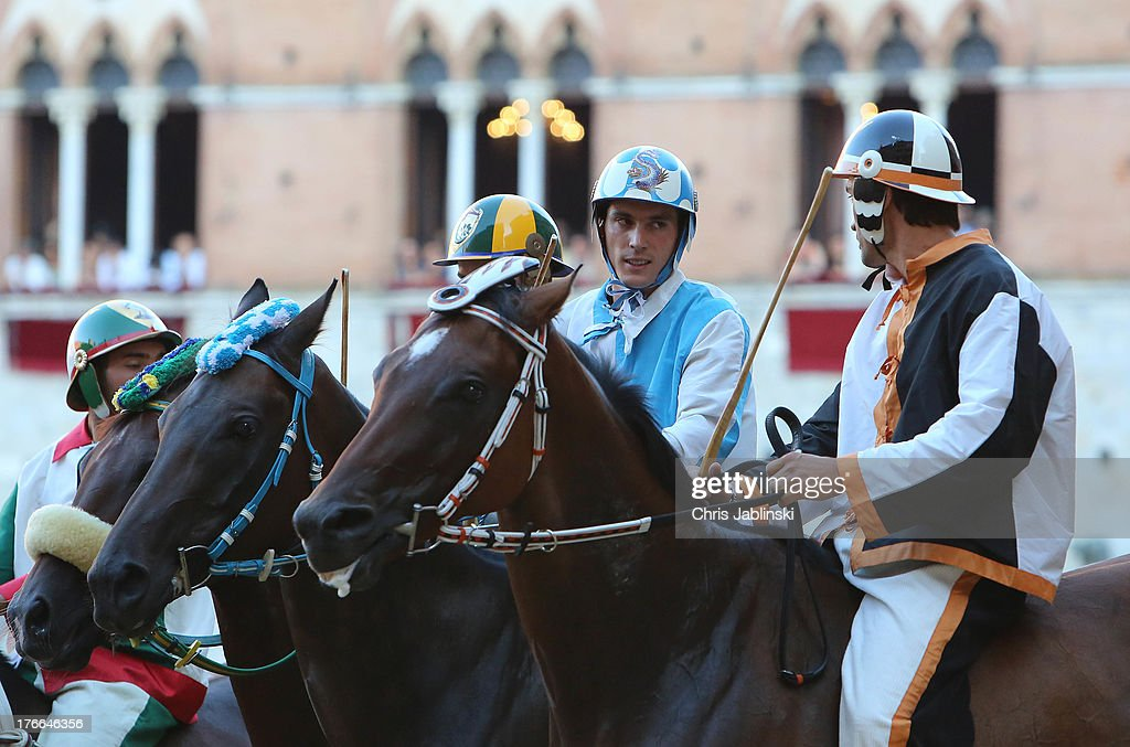 Giovanni Atzeni (C), known as Tittia, prepares for the start of the Palio dell'Assunta horse-race at Piazza del Campo square on August 16, 2013 in Siena, Italy. The Palio races in Siena, in which riders representing city districts compete, and takes place twice a year in the summer in a tradition that dates back to 1656.