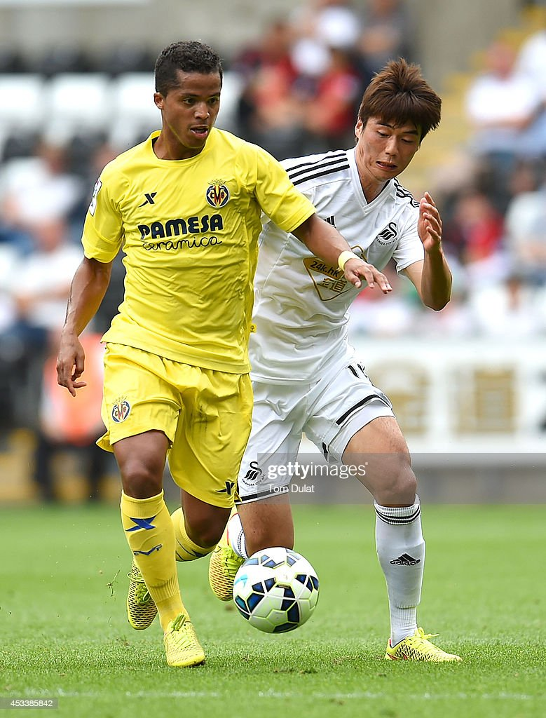 Giovanni Dos Santos of Villarreal and Ki Sung-Yueng of Swansea City in action during a pre season friendly match between Swansea City and Villarreal at Liberty Stadium on August 09, 2014 in Swansea, Wales.
