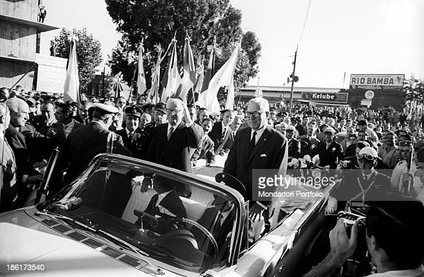 Giovanni Gronchi the President of the Italian Republic on an official visit to South America stands inside a convertible car and salutes the sea of...