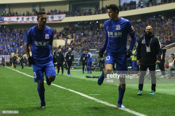 Giovanni Moreno of Shanghai Shenhua celebrates with Fredy Guarin after scoring his team's first goal during the 2nd round match of CSL Chinese...