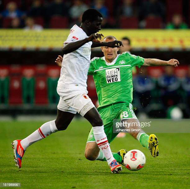 Giovanni Sio of Augsburg fights for the ball with Thomas Kahlenberg of Wolfsburg during the Bundesliga match between FC Augsburg and VfL Wolfsburg at...