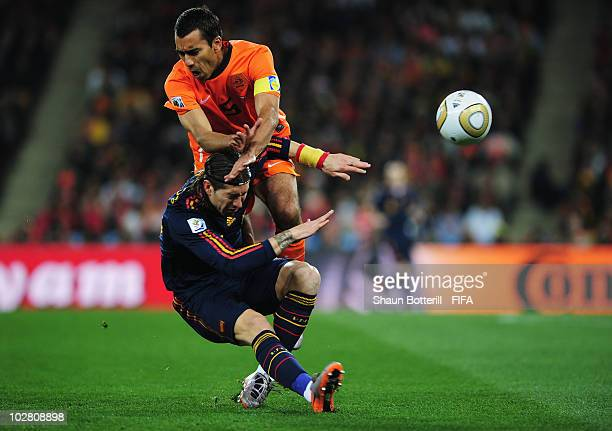 Giovanni Van Bronckhorst of the Netherlands challenges Sergio Ramos of Spain during the 2010 FIFA World Cup South Africa Final match between...