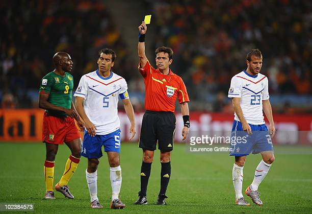 Giovanni Van Bronckhorst of the Netherlands receives a yellow card from referee Pablo Pozo during the 2010 FIFA World Cup South Africa Group E match...