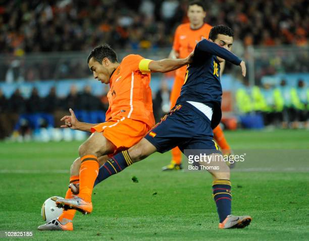 Giovanni Van Bronckhorst of the Netherlands tackled by Pedro of Spain during the 2010 FIFA World Cup Final between the Netherlands and Spain on July...
