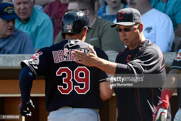 Giovanny Urshela is congratulated by manager Terry Francona of the Cleveland Indians after scoring in the third inning against the Chicago Cubs at...