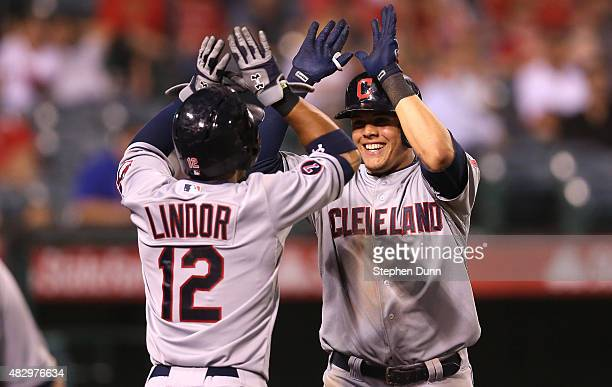 Giovanny Urshela of the Cleveland Indians celebrates with Francisco Lindor as he returns to the dugout after hitting a two run home run in the 12th...