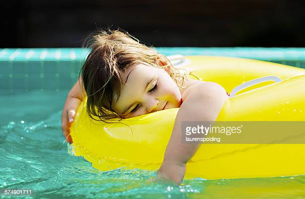 Gir lying in a rubber ring in swimming pool