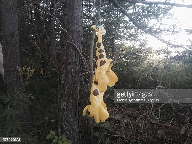 Giraffe Balloon Hanging From String Against Tree