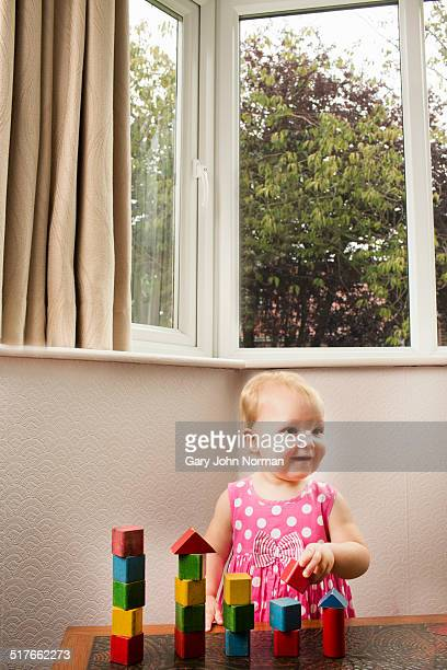 Girl 18 months building towers with wooden bricks
