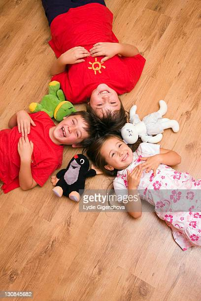 Girl, 4 years, and boys, 6 and 11 years, lying on the floor, laughing, with plush toys