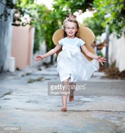 girl, 6 years old running with cardboard wings