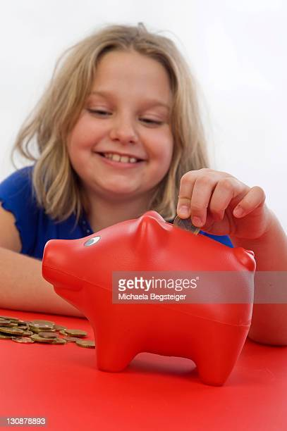 Girl, 8 years old, putting money into her piggy bank