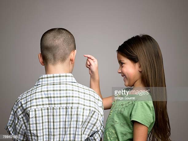 Girl about to poke boy in ear