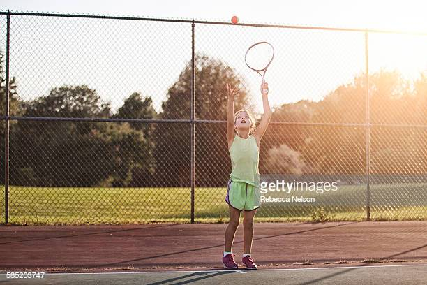 girl about to serve tennis ball